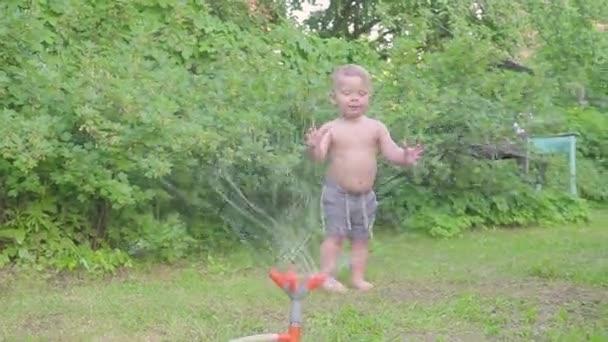 Ragazzino felice divertirsi fuori con lo spruzzatore dacqua nel giardino estivo. Slow motion