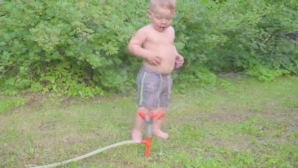 Glückliche kleine Junge Spaß außerhalb mit Wasser Sprinkler im Sommergarten. Slow-motion
