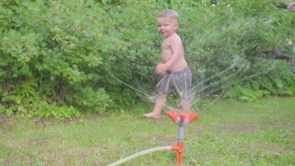Ragazzino sveglio divertirsi fuori con lo spruzzatore dacqua nel giardino estivo. Slow motion