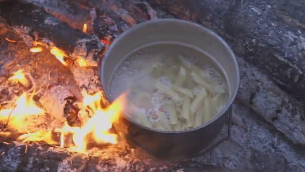 Főző üst, tábortűz, esti erdőben a tészta. A szakács az étel moccan kanállal. Közeli kép: