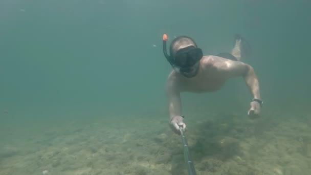 Ein Mann taucht und macht ein Selfie unter Wasser. winkt dir mit der Hand zu und mag