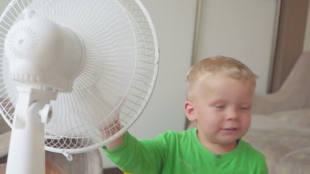 childhood, home concept - cute little boy with big cooling fan