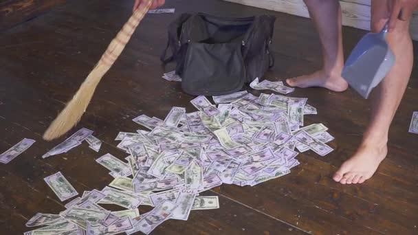 Koště dobře mete dolarů v scoop smetí na podlaze. Koncept nečekané bohatství