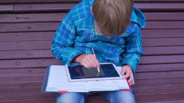 portrait of a schoolboy who does homework with a textbook and a tablet on the outdoors