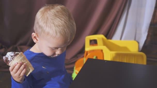 chlapec, jíst zmrzlinu sedí v židličce. roztomilé dítě těší zmrzlina v oplatkovém kornoutku. vypadá ke