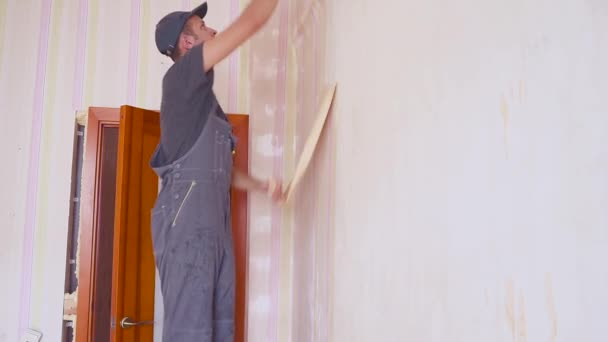 The worker takes the wallpaper off the