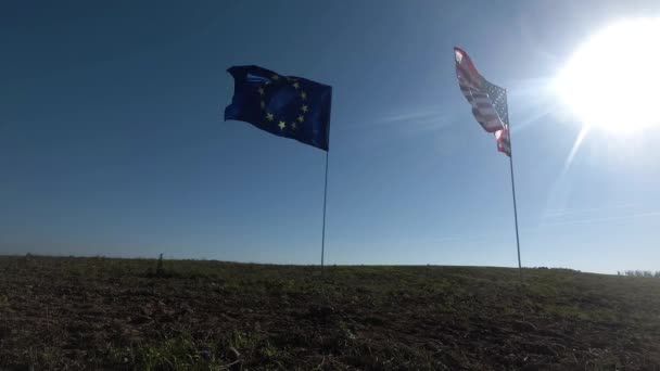 Flags of the United States of America and European Union waving together on the wind. Real shot in landscape.