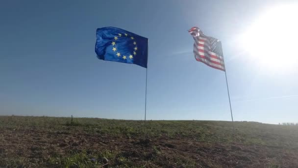 Flags of the United States of America and European Union waving together on the wind. Real shot in landscape
