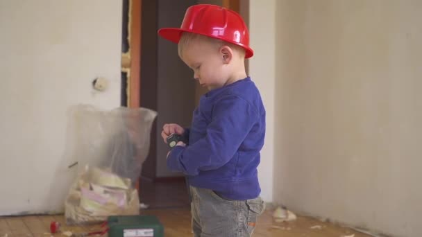 Little builder in red helmet with yellow ruler tape in hands in the apartment under repair. Construction concept.