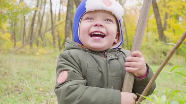 portrét chlapce, který se hraje v podzimním parku a usmívá se