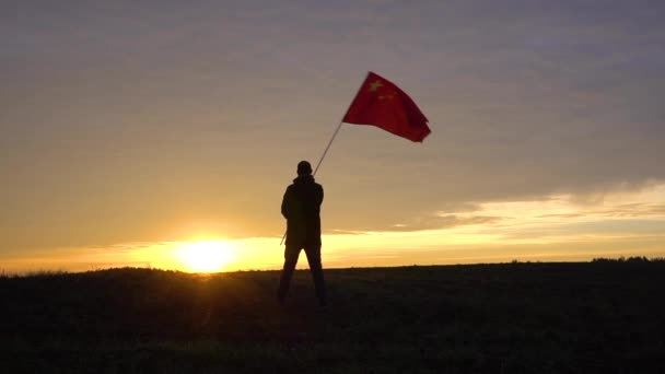 Successful silhouette man winner waving China flag in the landscape.