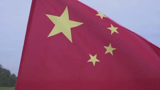 schwenkt die chinesische Flagge. Flagge der Volksrepublik China gegen den blauen Himmel.