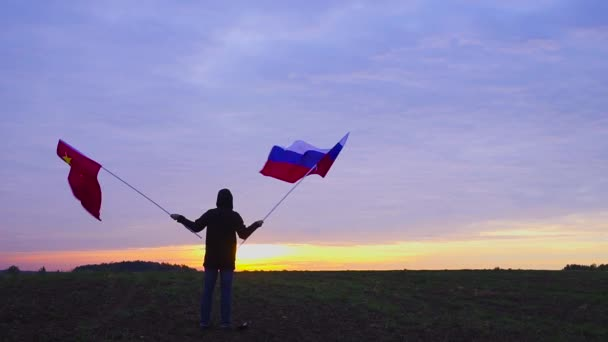 Footage of Russian and Chinese flags blowing in the wind. waving flags in a landscape. Russian China Flag.