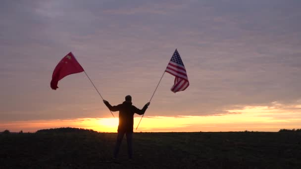 Footage of American and Chinese flags blowing in the wind. waving flags in a landscape. USA China Flag.