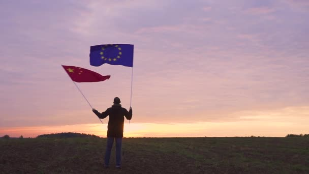 Footage of EU and Chinese flags blowing in the wind. waving flags in a landscape. EU China Flag.