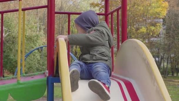 fröhlicher Junge reitet auf Spielplatz den Hügel hinunter