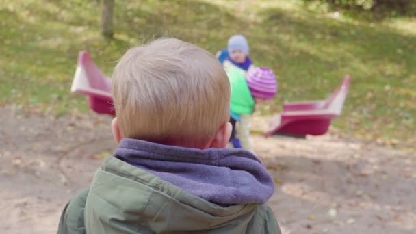 Boy watching kids play