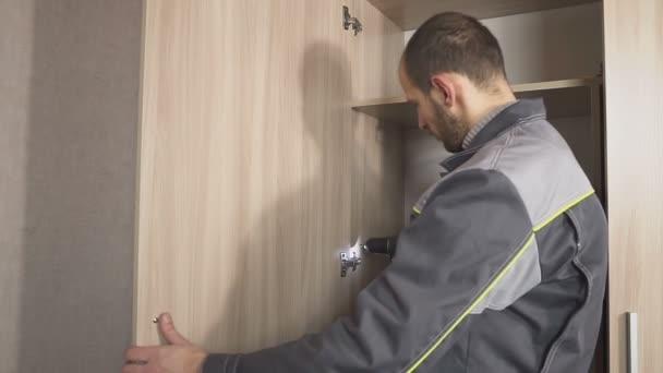 Mann mit einem Schraubenzieher montiert Möbel