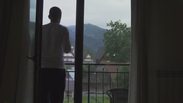 Young Man goes from his room to the balcony with a glass of wine , Look at Mountains