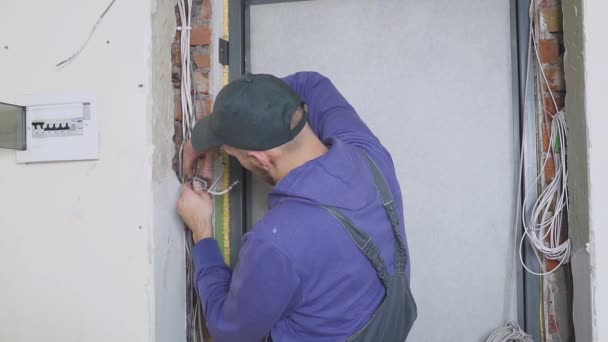 un elettricista sul lavoro che fissa il cavo di cablaggio