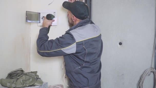 Jeden elektrikář v práci pokládání kabelových vedení s zařízení a nástrojů. Šroubovák.
