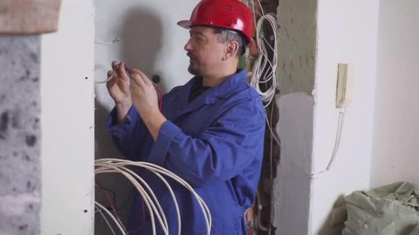 Un elettricista sul lavoro posa cavo di cablaggio con attrezzature e strumenti. Cacciavite.
