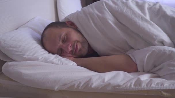 Alvó ember felébred egy franciaágy. Oldalnézet, közepes lövés.