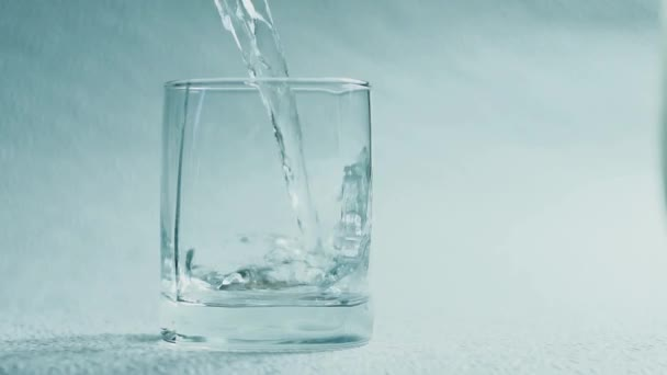 Vodu nalijte do sklenice na bílém pozadí