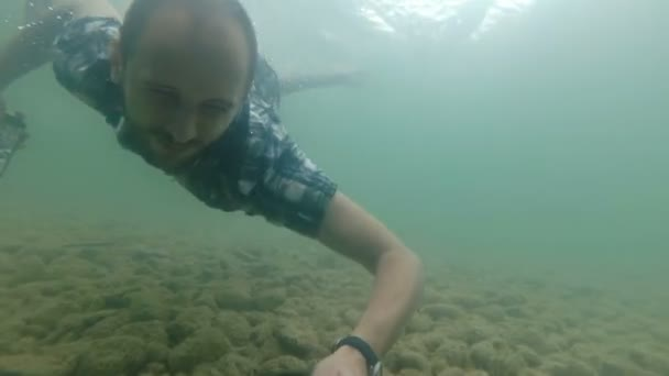 Businessman using smartphone underwater in slow motion. Natural lake