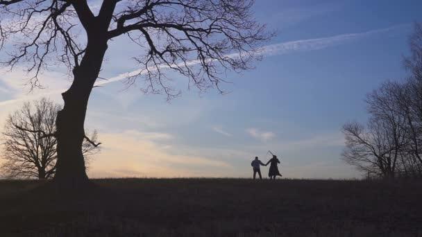 Der Sensenmann sucht sich ein neues Opfer und führt das Opfer in den Tod. Sonnenuntergang Silhouette. Konzept des Todes