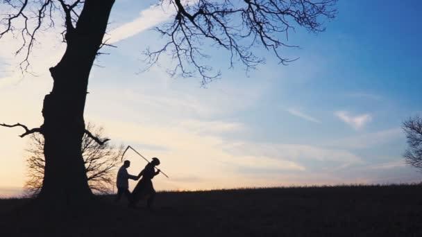 Der Sensenmann sucht sich ein neues Opfer und führt das Opfer in den Tod. Sonnenuntergang Silhouette. Das Konzept des Todes und der Kampf ums Leben