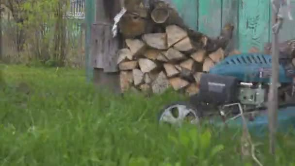 Lawn mower cutting green grass in backyard. Gardening background.