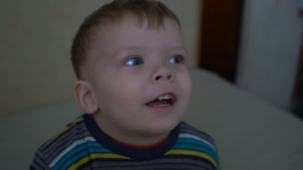 Close up of a two years old boy is watching TV in a dark room.