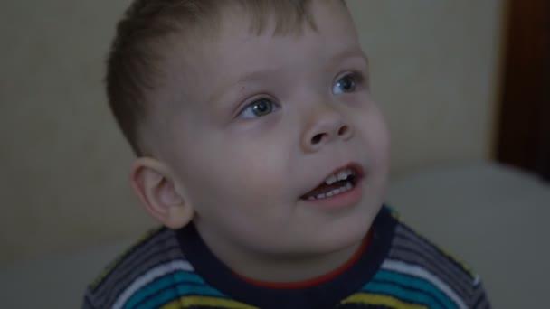 Detailní záběr na dva roky starý chlapec sleduje film na domácí projektor.