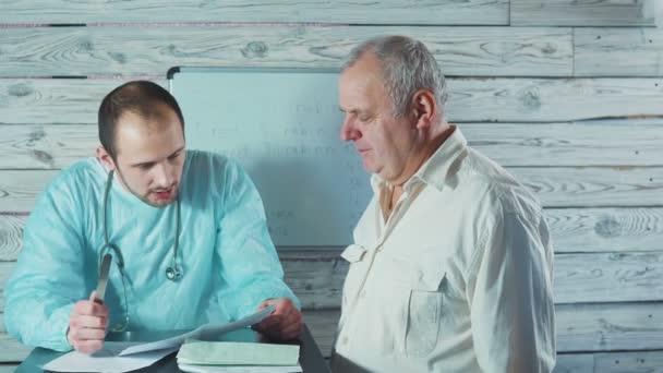 Menschen, Medizin und Gesundheitswesen Konzept - Arzt sucht Elektrokardiogramm Ergebnisse und empfehlen Therapie Senor Patienten Arztpraxis im Krankenhaus