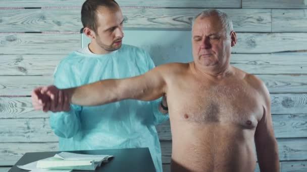 Junge Physiotherapeuten arbeiten mit älteren Patienten in der Klinik. Prüfung der Wunden arm.
