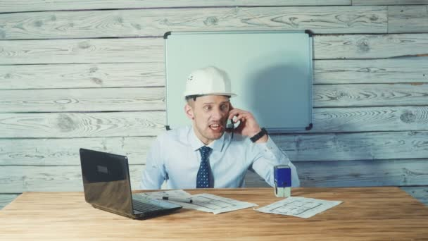 ein wütender, nervöser Architekt, der an Zeichnungen neuer Projekte arbeitet und am Telefon spricht.
