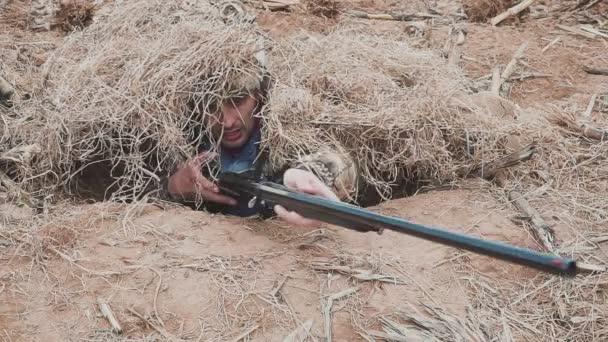 Liba vadász bujkál a száraz fű egy vadászpuska a kezében