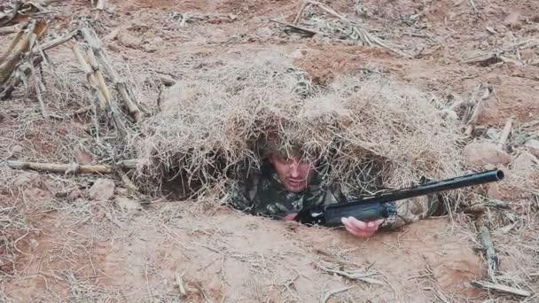 Lovec hus se schovává v suché trávě s loveckou puškou v rukou