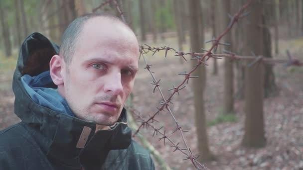 Mann am Zaun mit Stacheldraht. Konzept zur illegalen Einwanderung und zum Schmuggel. Drogenhandel.