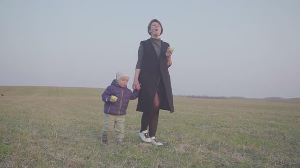 Mutter und Sohn essen einen Apfel in der Außenlandschaft. über das Feld gehen und Äpfel essen. Reiseabbruch