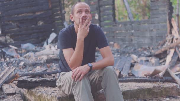 Portrét smutného muže na pozadí spáleného domu, po požáru. Následky nehody při požáru. Ruiny po požáru, o zoufalství.