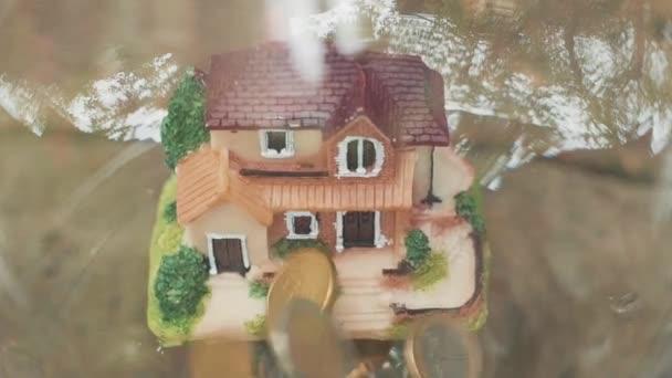 padá na peníze domů. Peníze na mince a model domu. Koncepce financí a bankovnictví. Zpomaleně