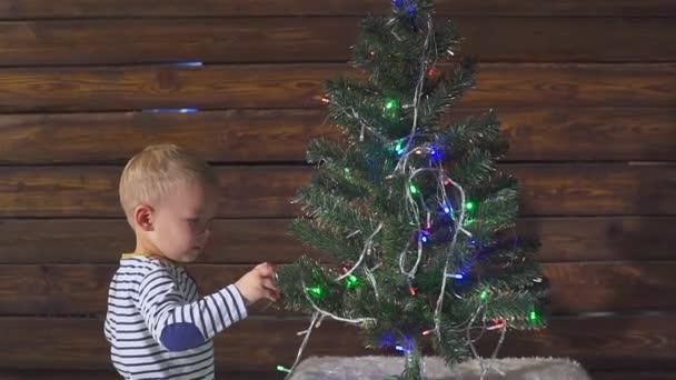 zweijähriger Junge spielt mit Weihnachtsspielzeug am Weihnachtsbaum, aus nächster Nähe. Porträt eines Kindes neben einem Weihnachtsbaum.
