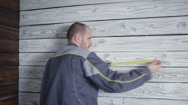 Pracovník měří dřevěné zdi s pravítkem