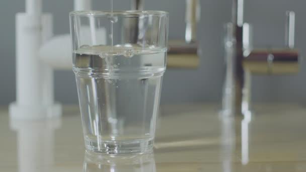 Víz Önt egy pohár egy adagoló. Tiszta víz, szűrés, egészség.