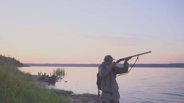Sziluettje a vadász egy kacsavadászat közelében egy gyönyörű tó. Lövés vadász.