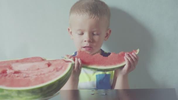 glücklich lächelnder Junge appetitlich essen rote Wassermelone und Saft fließt unter dem Mund