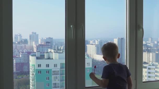 Silueta malého chlapce stojícího u okna na pozadí velkého města s mrakodrapy. Portrét.