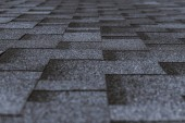 Měkká střecha vedle sebe šedý zrnitý textury na vrcholu vesnice dům; šedý měkký střešní krytiny zahrnující budovu, zaměřit se na střední vzdálenosti, malá hloubka ostrosti